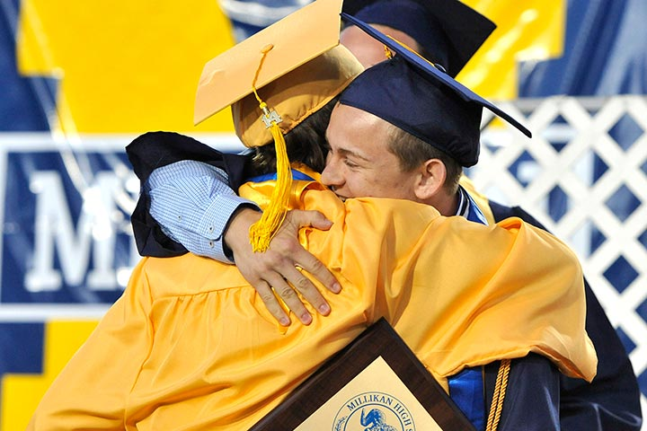 Millikan grads hug on stage