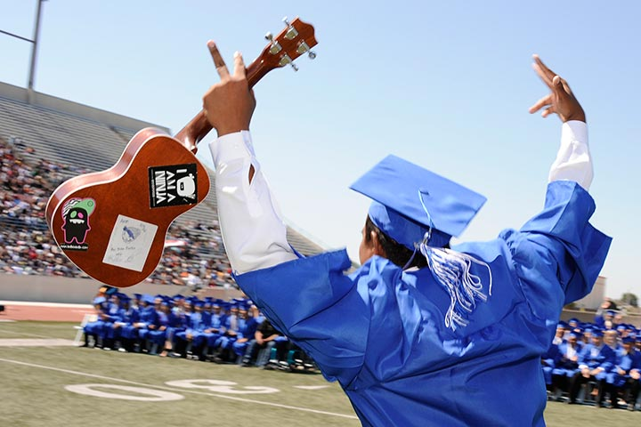 Grad with guitar in hand on stage