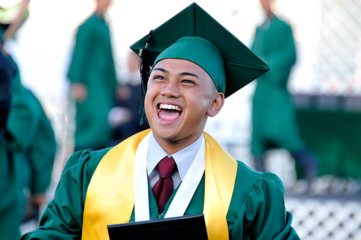 Male Cabrillo graduate smiles with diploma