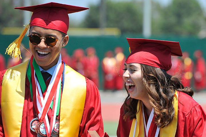 Two Lakewood students laugh together at graduation