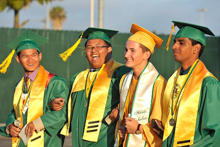 Four male Poly students walk at graduation together