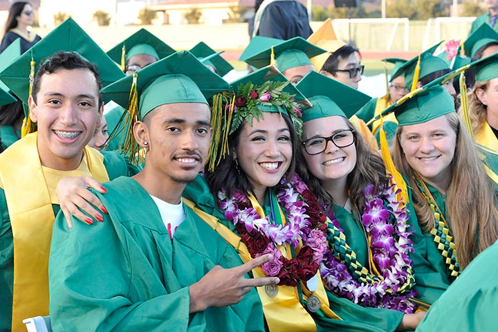 Poly students pose together at graduation ceremony