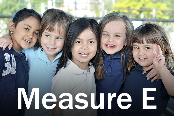 Measure E Logo with four children in background