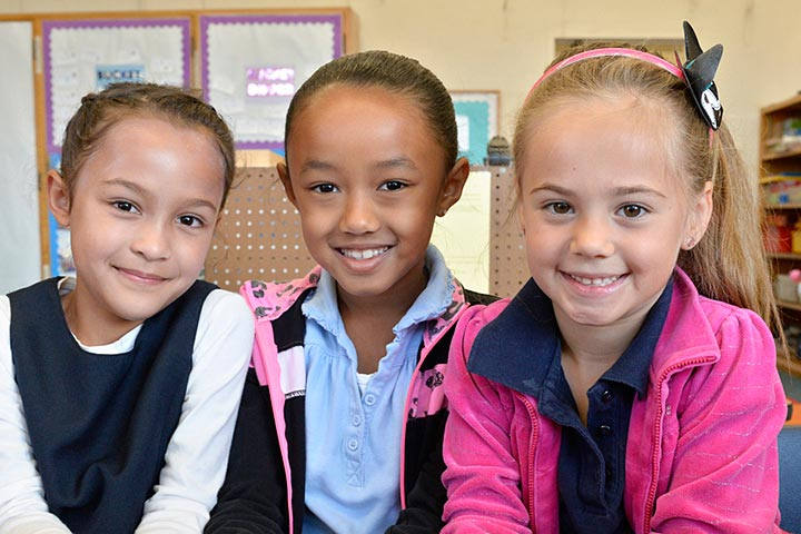 Three elementary girls posing for the camera