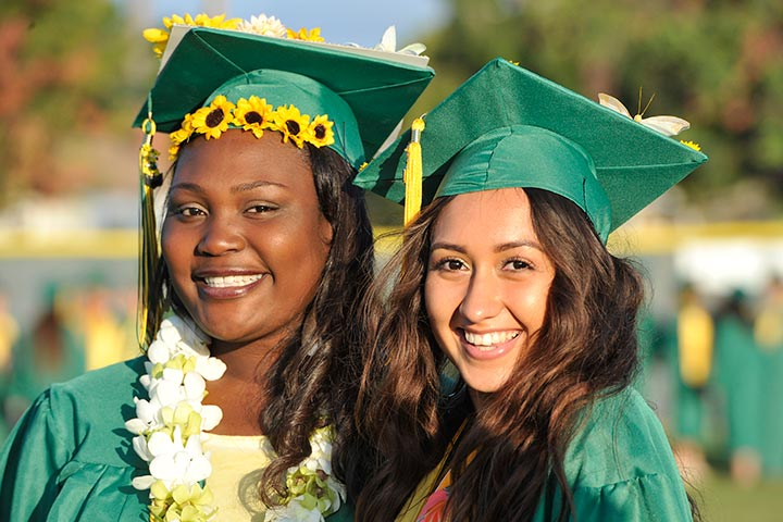 Two female grads smile