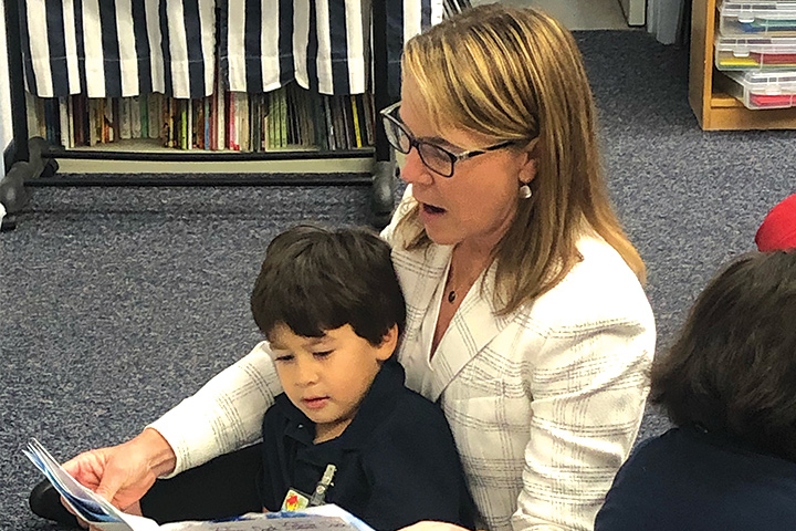 Superintendent Baker reading to a young student.