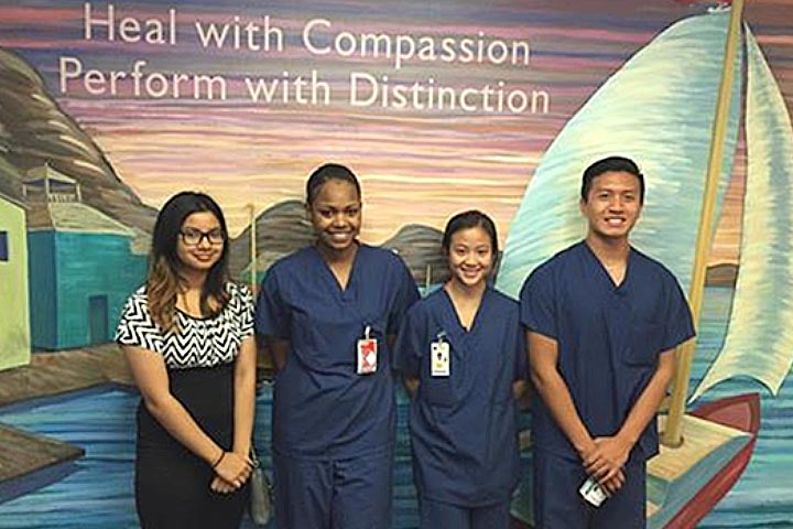 Four students in hospital scrubs pose for picture
