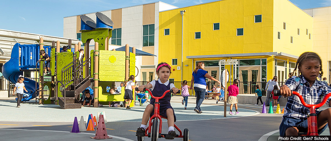 Preschoolers ride tricycles at Educare school