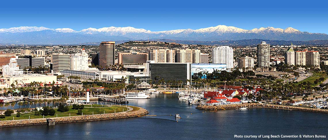 Panoramic photo of downtown Long Beach with ocean in the foreground and skyline and mountains in the background.