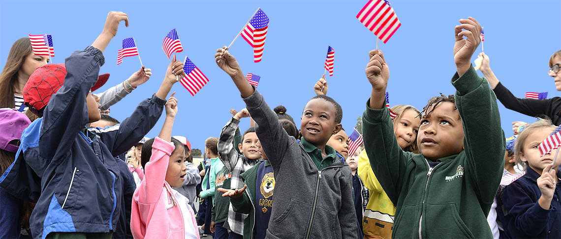 Bixby students wave American flags, welcoming Veterans on the school playground.
