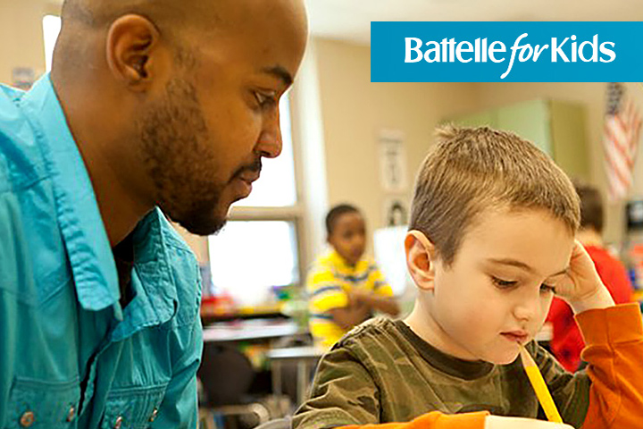 Battelle image - Teacher works with student at his desk