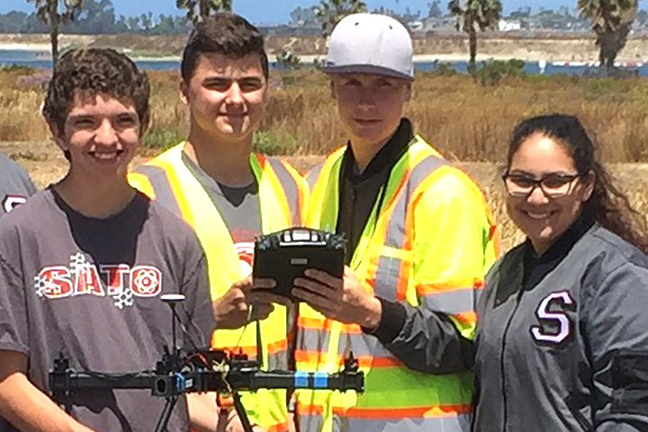 Four students pose with a drone they built.