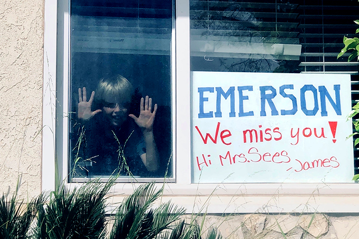 Emerson student at home with sign