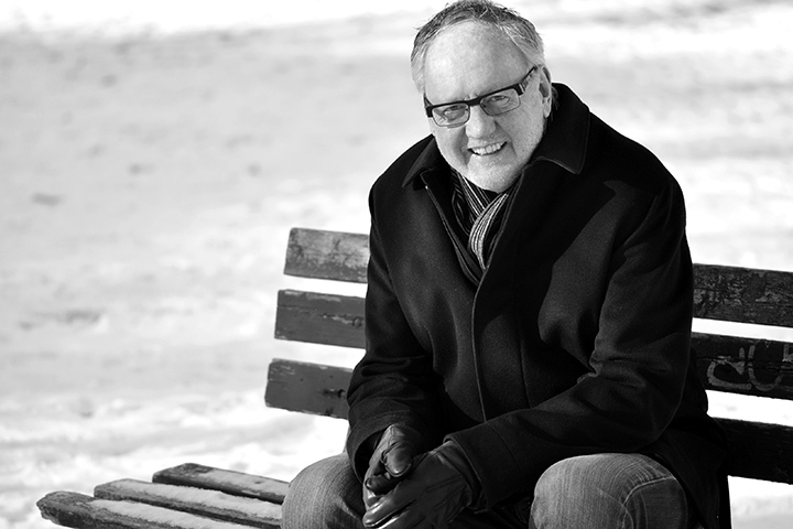 Black and white photo of Michael Fullan sitting on a park bench.
