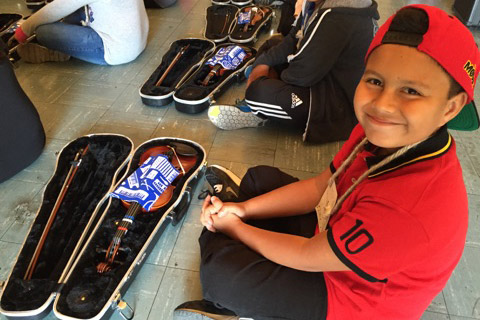 Young student sits with his violin and case in front of him