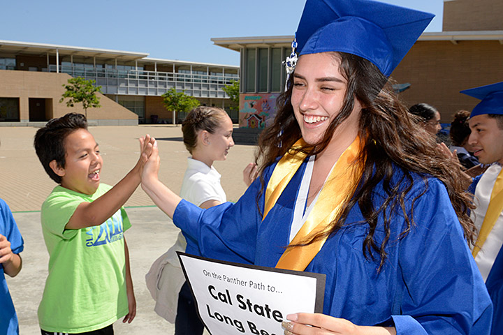 Jordan grads in caps and gowns high-five younger students.