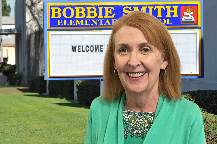 Teacher Librarian Mary McCarthy with Bobbie Smith Elementary Backdrop
