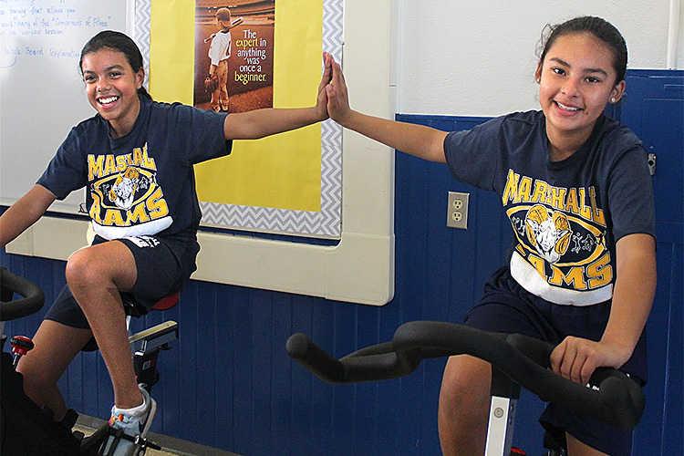Students on exercise equipment in new fitness room at Marshall Academy