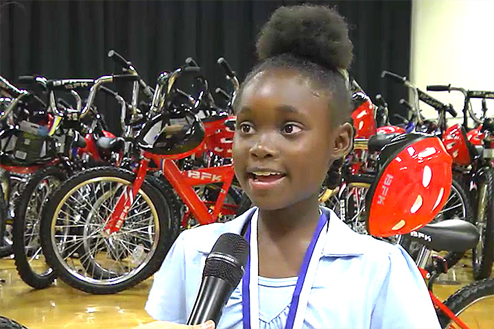Student talks to a cameraman about receiving a new bike.