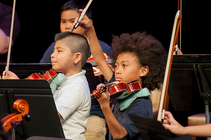 Students play violins as part of the orchestra.