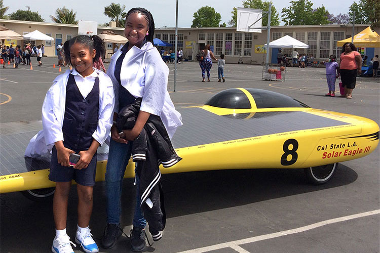 Two female students pose in front electric car