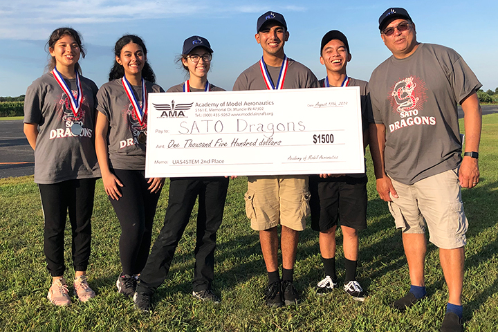 Members of Sato's Drone Team pose with oversized check for $1,500