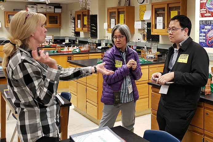 Teacher Christine Appel speaks with visitors from Singapore.