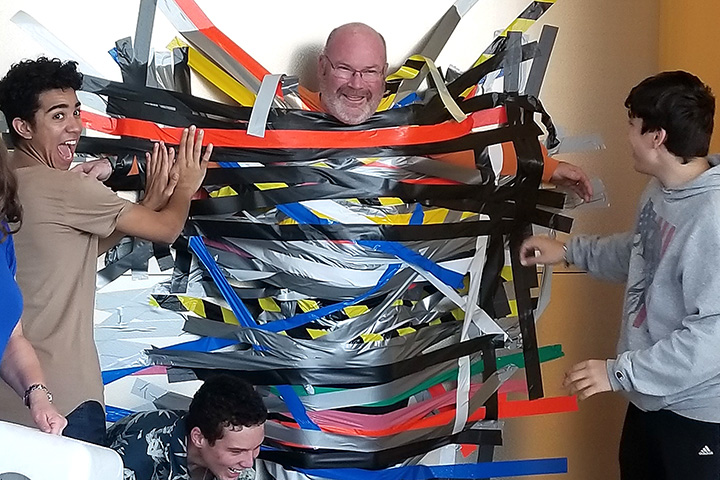 Principal Rockenbach is duct taped to a wall by students.