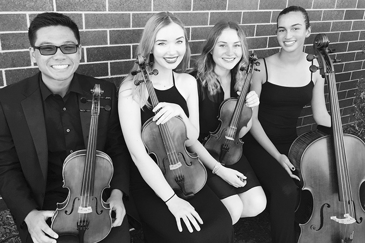 The Wilson High School String Quartet pose on park bench